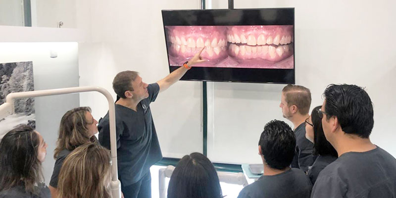 Dr. Mitrani with a group of students, pointing to a TV with side by side comparision images of front teeth.