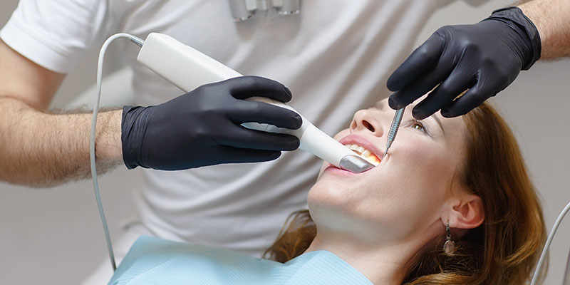 dentist chair with a female patient being scanned with a laser