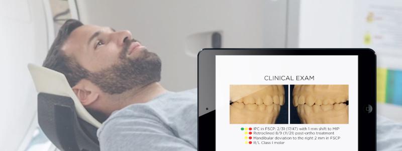 man lying back in the dentist chair, in the foreground is an ipad with the new module on screen.