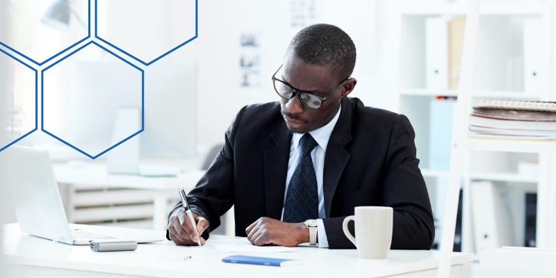 Man filling out paperwork while sitting at a desk