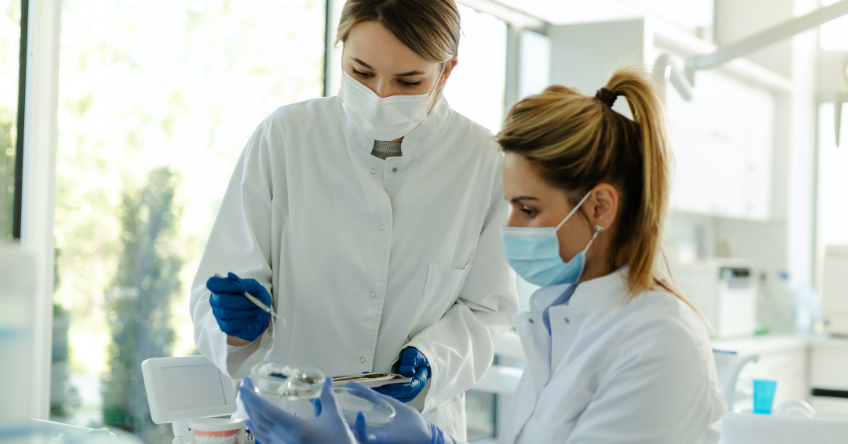 Featured Image: In a dental office, two women wearing lab coats and face masks holding and looking dental equipment together