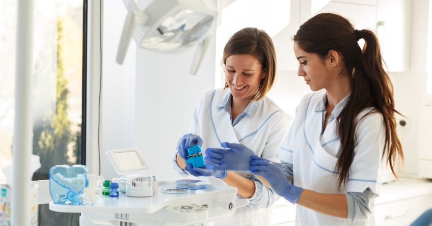 Two women in lab coats working with a sample in a dental office