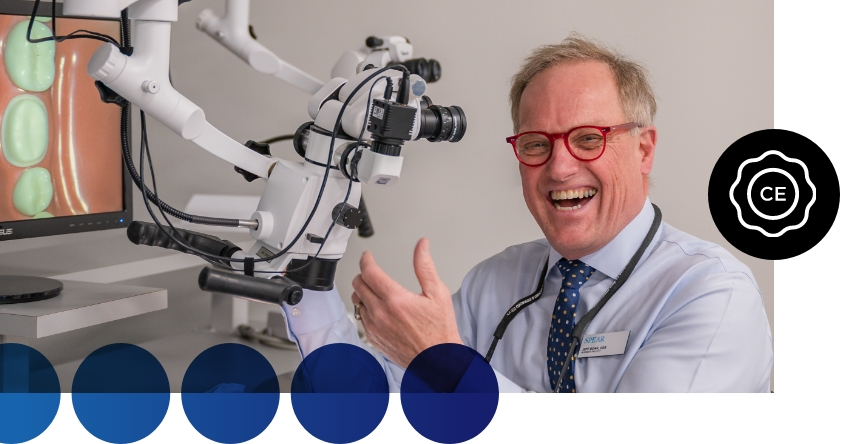 Dr Lineberry smiling in a room with dental equipment. Black circle with white CE icon overlayed