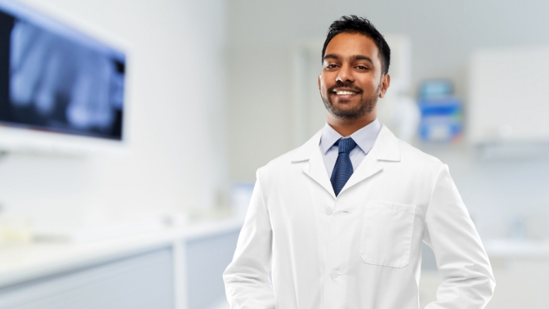 Male doctor smiling in front of blurred patient examination room with xray of teeth on a screen
