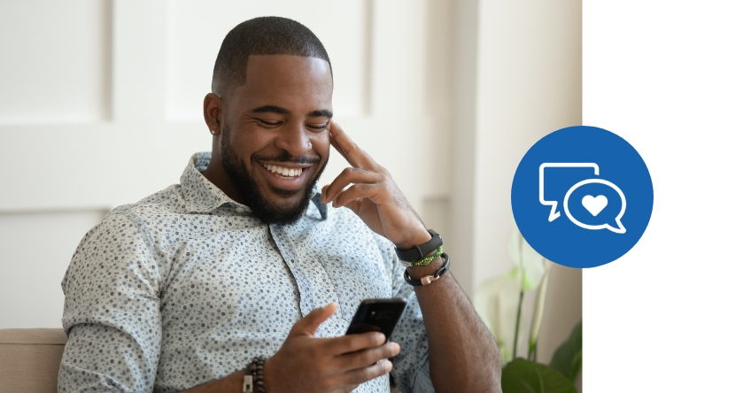 Man laughing looking at his phone with social media 'comment' and 'like' icons overlayed in a blue circle