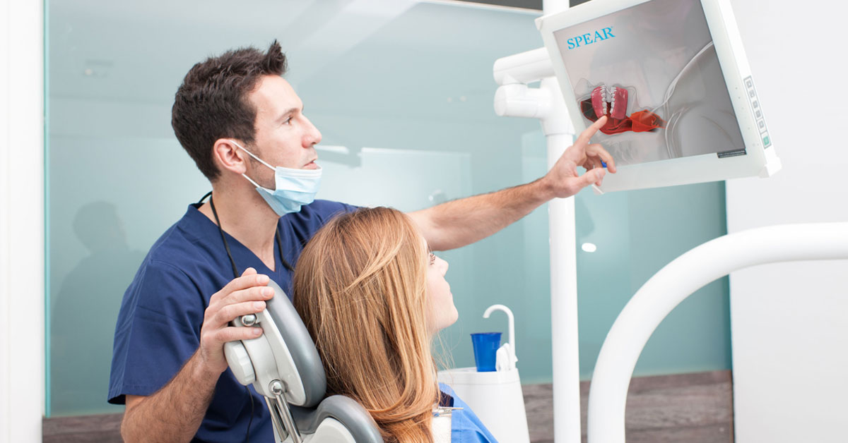doctor with patient in a dental chair pointing to her xrays