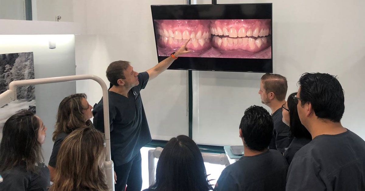 Ricardo pointing to a tv screen with a side by side mouth comparision