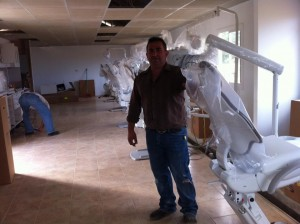 A man stands beside new dental chairs and equipment.